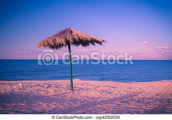 Old umbrella on the beach, retro toned image - csp42302030