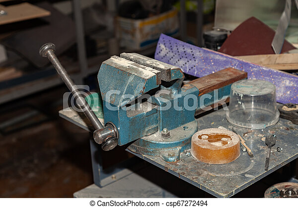 Old vice of blue color for a strong clamping of objects and further industrial work in a workshop for production. Tool for Manufacturing - csp67272494