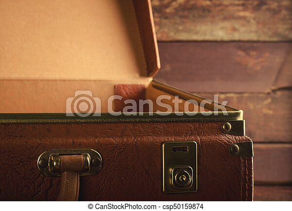 Old vintage, retro open suitcase on dark background. Front view, horizontal, toned