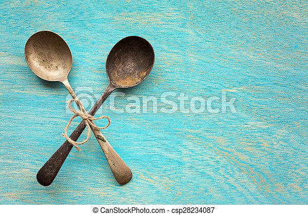 Old vintage spoons on blue wooden background - csp28234087