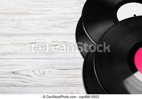 Old vinyl record on the bright wooden table, selective focus and toned image. Copy space - csp49610553