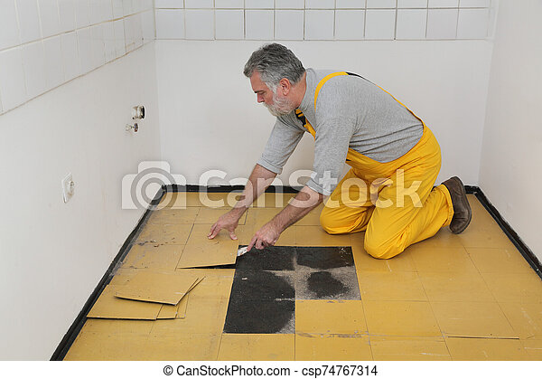 Old Vinyl Tiles Removal From Floor In A Kitchen Worker Removing Old Vinyl Tiles From Kitchen Floor Using Spatula Trowel Tool Canstock