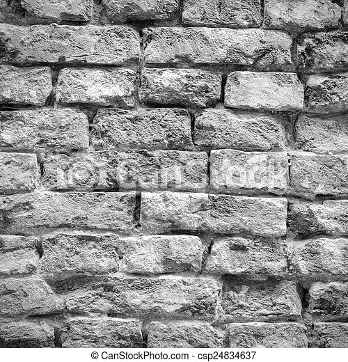 Old weathered and battered brick wall texture in black and white - csp24834637