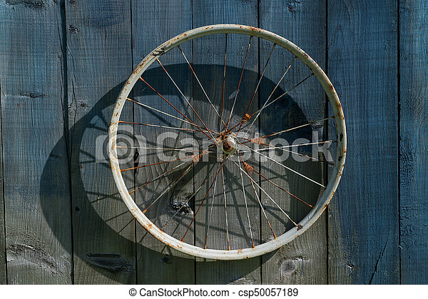old wheel from a bicycle on a wooden background - csp50057189