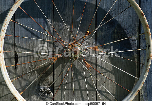 old wheel from a bicycle on a wooden background - csp50057164