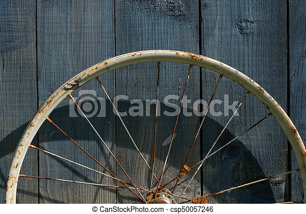 old wheel from a bicycle on a wooden background - csp50057246