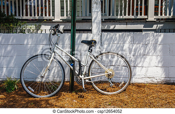 Old White Bicycle Chained to Green Pole - csp12654052