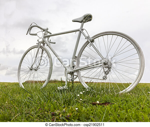 Old White Bicycle in a Field - csp21902511