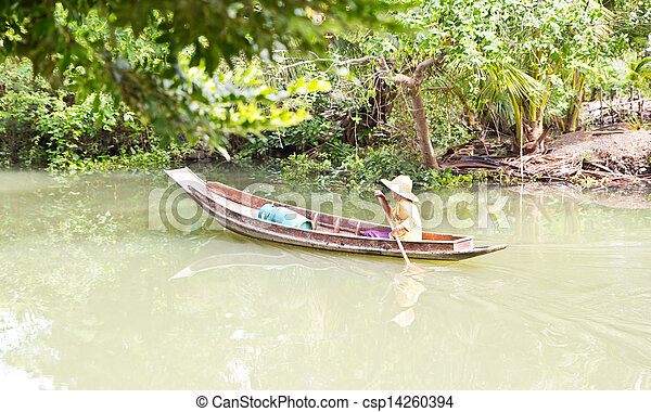 Old woman rowing a wooden on the river - csp14260394