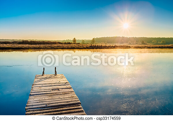 Old wooden boards pier on Calm Water Of Lake, River - csp33174559