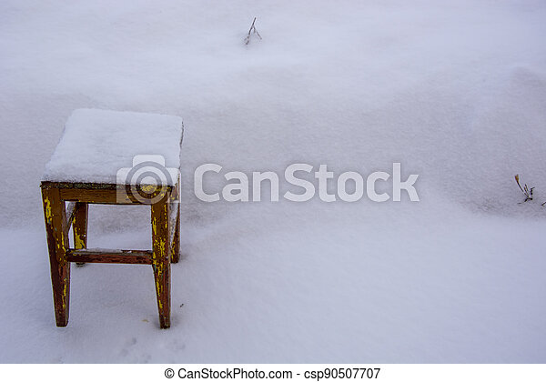 Old wooden chair in the snow. Stool in a snowdrift. There is a lot of snow in the garden in winter. - csp90507707