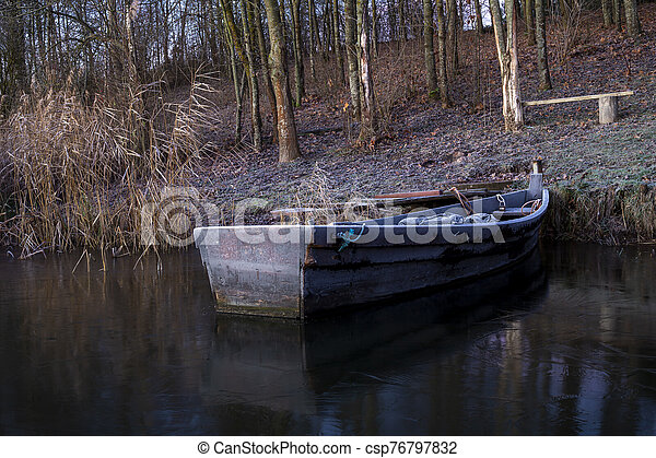 Old wooden dinghy moored to the shore of a lake - csp76797832