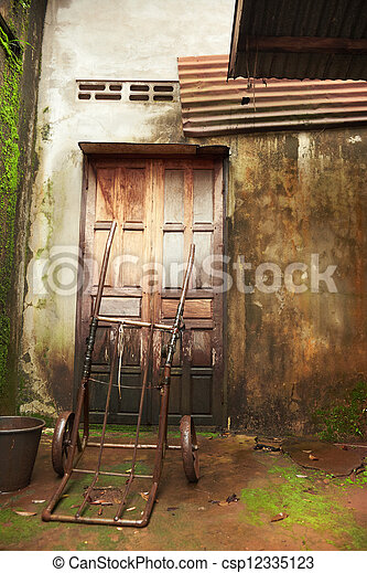 Old wooden door and wall of a house damaged by moisture - csp12335123