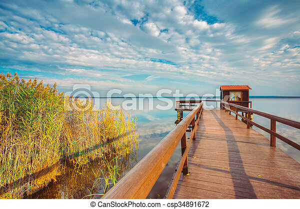 Old wooden pier for fishing, small house shed and beautiful lake - csp34891672
