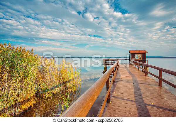 Old wooden pier for fishing, small house shed and beautiful lake or river - csp82582785