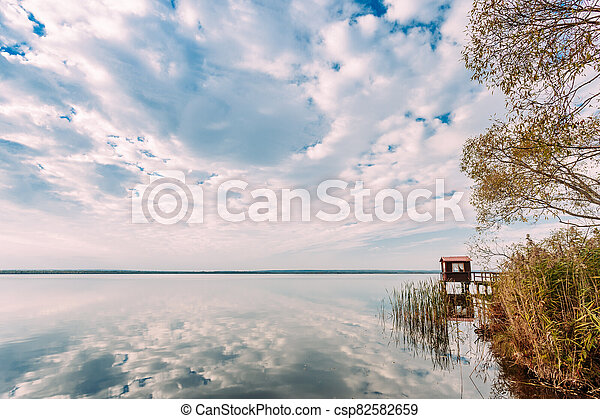 Old Wooden Pier For Fishing, Small House Or Shed And Beautiful Lake Or River - csp82582659