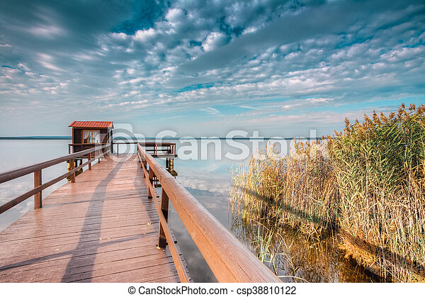 Old wooden pier for fishing, small house shed and beautiful lake - csp38810122