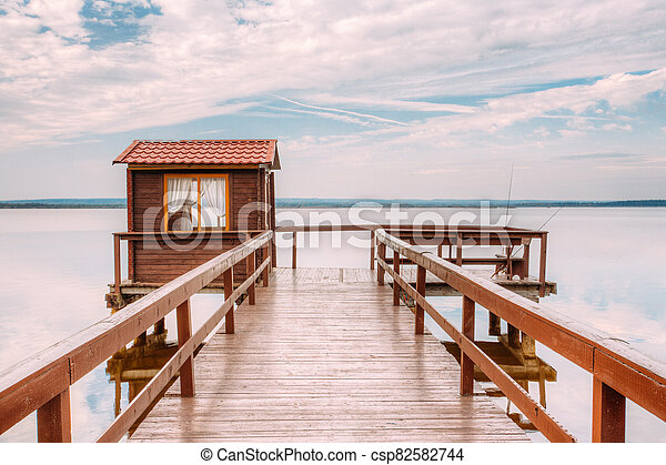 Old wooden pier for fishing, small house shed and beautiful lake or river - csp82582744