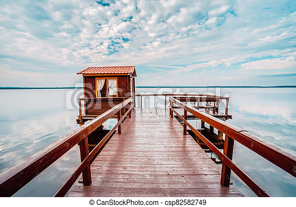 Old wooden pier for fishing, small house shed and beautiful lake or river - csp82582749