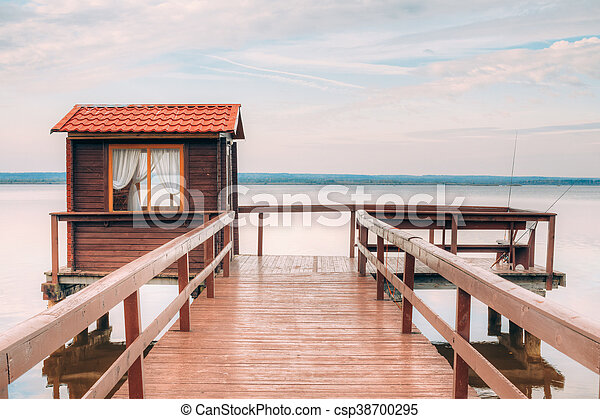 Old wooden pier for fishing, small house shed and beautiful lake - csp38700295