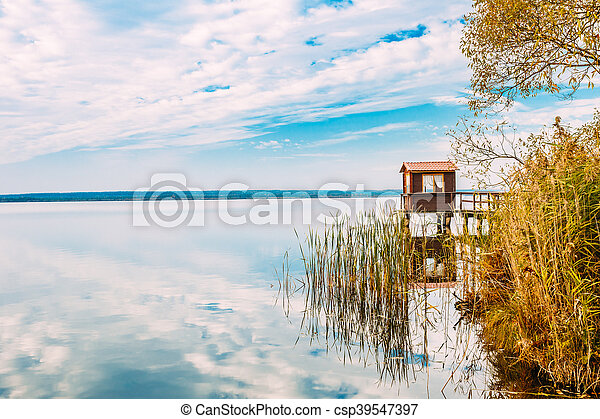Old Wooden Pier For Fishing, Small House Or Shed And Beautiful Lake - csp39547397