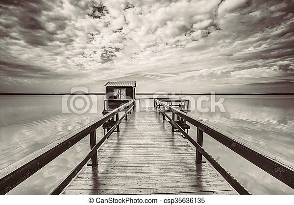 Old wooden pier for fishing, small house shed and beautiful lake - csp35636135