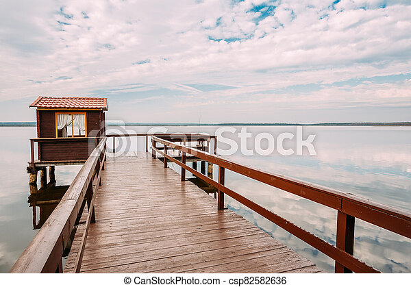 Old Wooden Pier For Fishing, Small House Or Shed And Beautiful Lake Or River - csp82582636