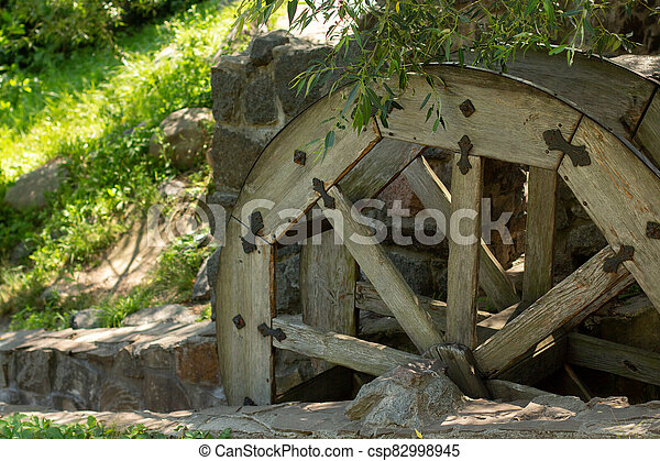 old wooden water pumping wheel on the river - csp82998945
