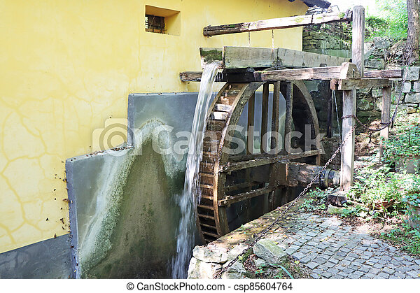 Old wooden wheel from a mill on the river - csp85604764