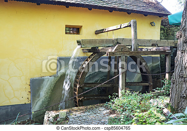 Old wooden wheel from a mill on the river - csp85604765