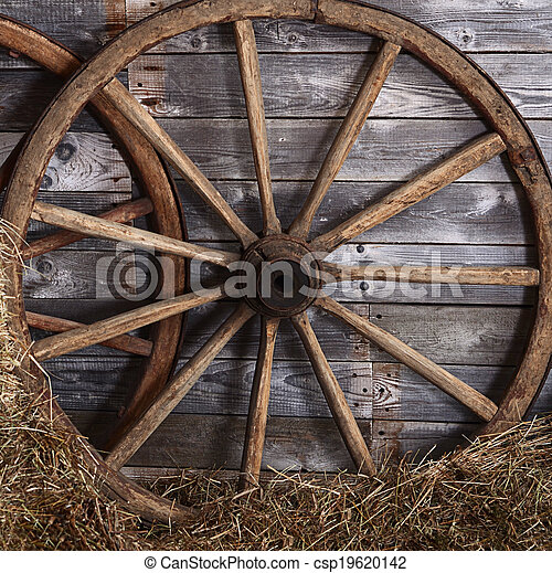 Old wooden wheel on a hay - csp19620142