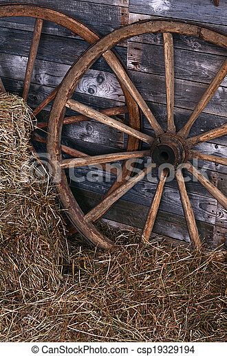 Old wooden wheel on a hay - csp19329194