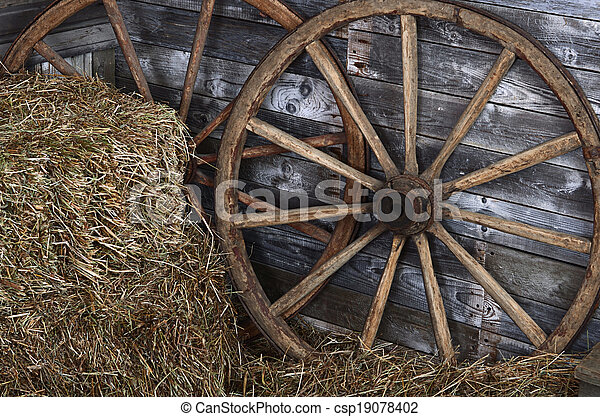 Old wooden wheel on a hay - csp19078402