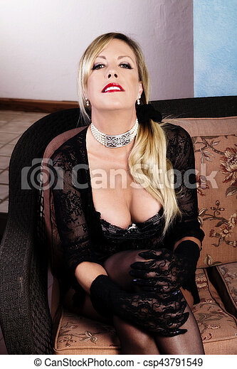 Older Blond Caucasian Woman Sitting In Lace Lingerie - csp43791549