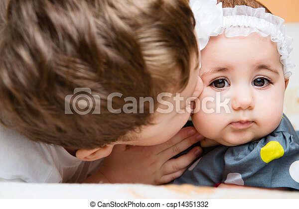 Older brother kissing his baby sister - csp14351332