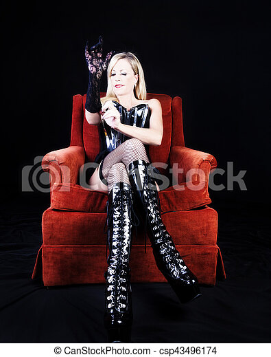 Older Caucasian Woman Sitting On Chair Boots And Corset - csp43496174