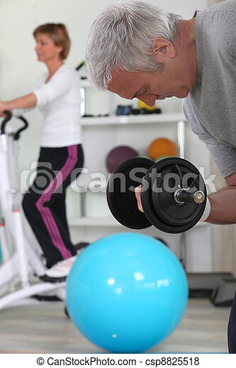 Older couple working out in gym - csp8825518