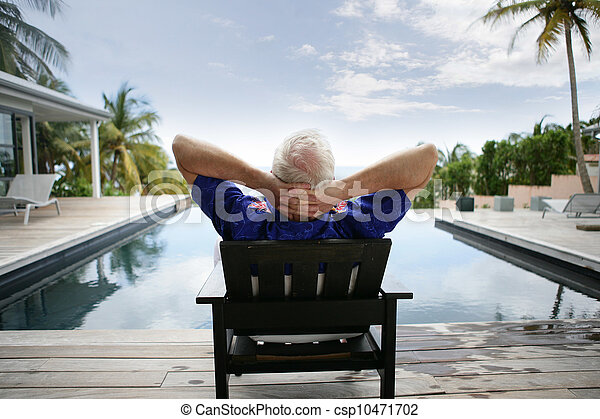 Older man relaxing by a luxurious pool - csp10471702