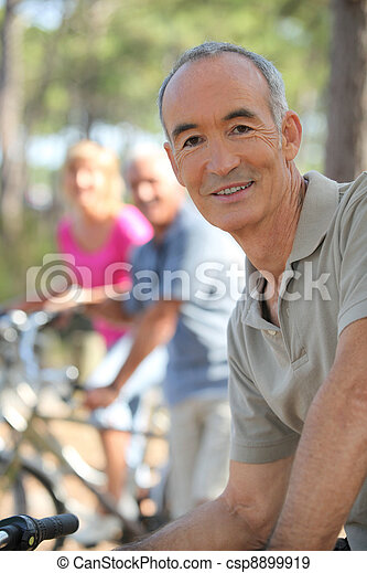 Older man riding a bike in the forest with friends - csp8899919