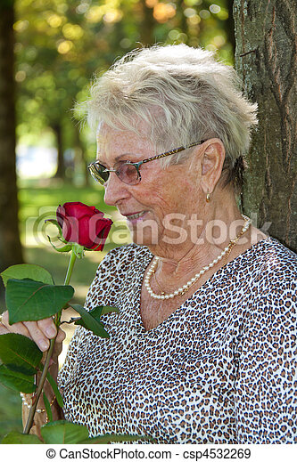 Older woman (senior citizen) smelling a red rose - csp4532269