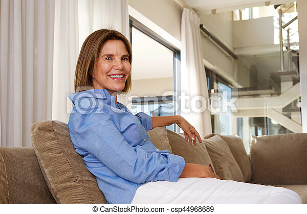 older woman sitting at home on sofa - csp44968689