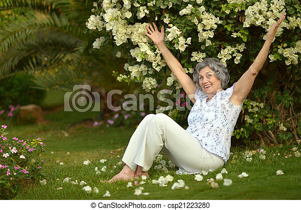 Older woman sitting with flowers - csp21223280