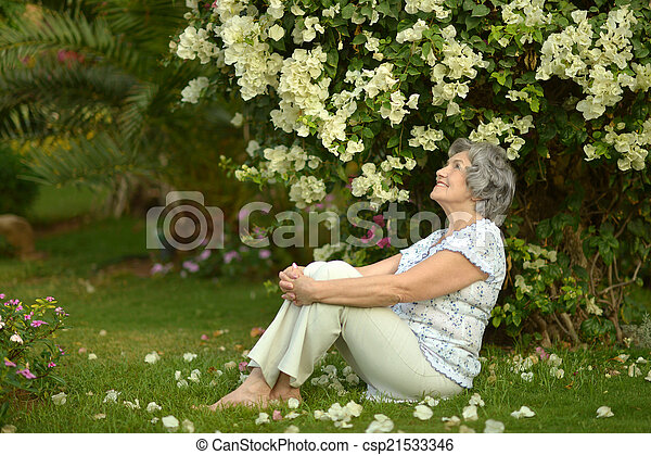 Older woman sitting with flowers - csp21533346