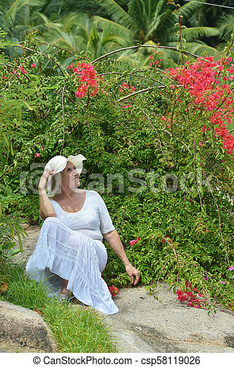 Older woman with red flowers - csp58119026