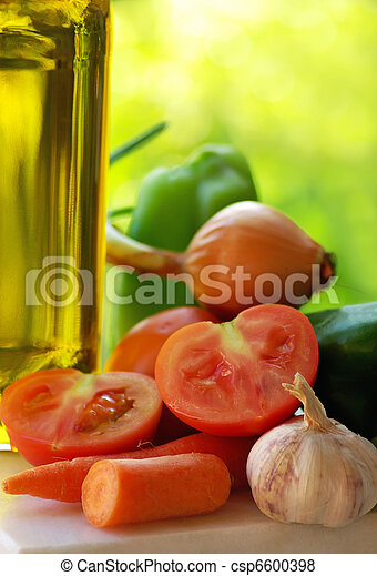 Olive oil and vegetables in green background. - csp6600398