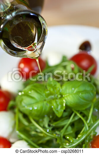 Olive Oil Dressing Pouring Onto Fresh Salad - csp3268011