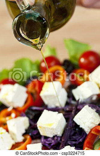 Olive Oil Dressing Pouring Onto Fresh Salad - csp3224715