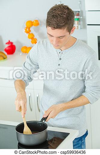 Un joven feliz cocinando marihuana en casa - csp59936436