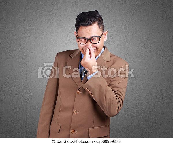 Un joven hombre de negocios huele mal - csp60959273