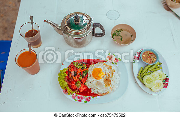 Omelet with vegetables, thai tea and soup on the table - csp75473522